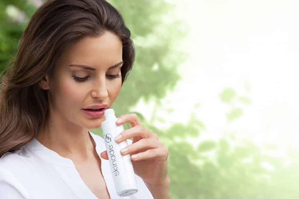 woman drinking skinade from bottle